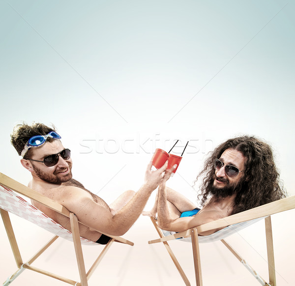 Stock photo: Two various guys resting together on the beach