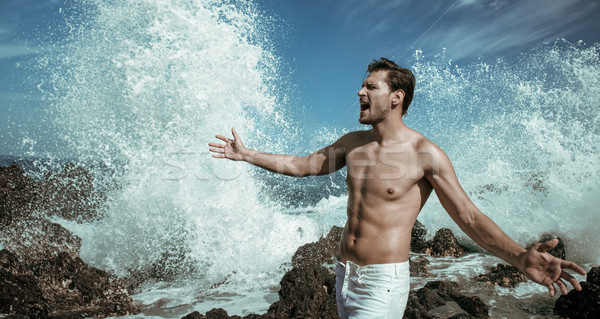 Handsome, muscular man with rough ocean in the background Stock photo © majdansky