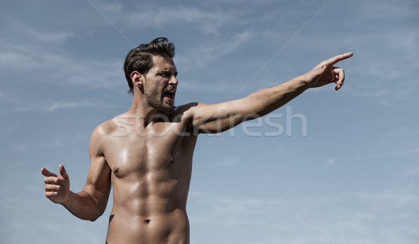 Portrait of a muscular man making a victory gesture Stock photo © majdansky