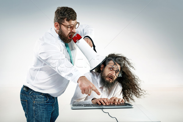 Angry boss yelling to an office worker Stock photo © majdansky