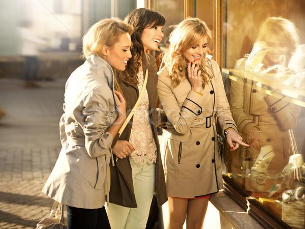 Three girlfriends looking at the shop window Stock photo © majdansky