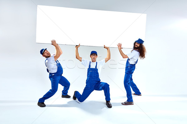 Funny craftsmen lifiting a heavy commercial board Stock photo © majdansky
