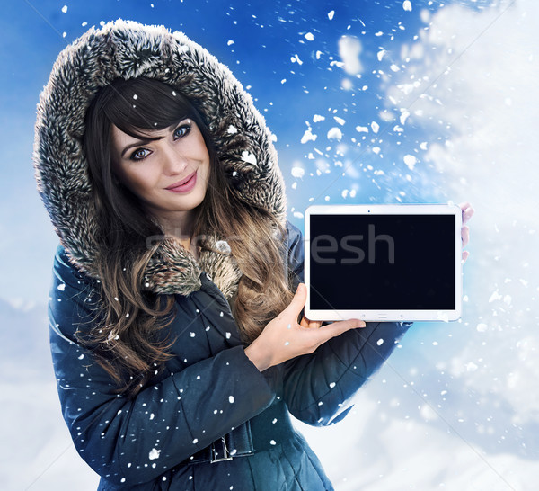 Brunette lady presenting a tablet outside - winter, chill day Stock photo © majdansky
