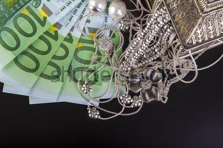 Silver jewelry and Euro on black - Silver jewelry and Euro on black background. Stock photo © manaemedia