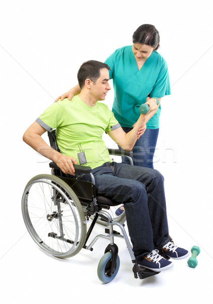 Physical therapist works with patient in lifting hands weights.  Stock photo © manaemedia