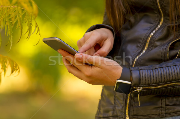 Young girl using smart phone in the park Stock photo © manaemedia