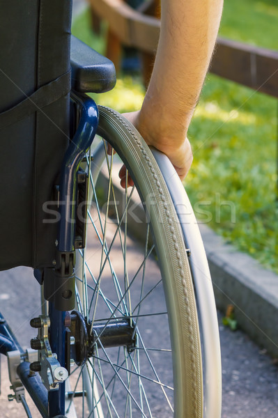hand of young man on the wheel of wheelchair  Stock photo © manaemedia