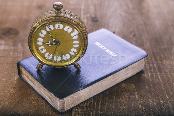 Stock photo: Holy Bible and old alarm clock on wood table
