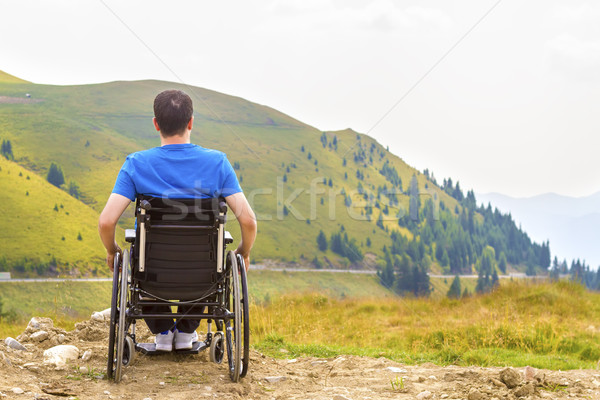 Young man in a wheelchair enjoying fresh air on a sunny day Stock photo © manaemedia