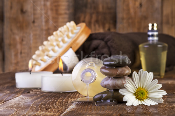 Stock photo: zen basalt stones and spa oil with candles on the wood