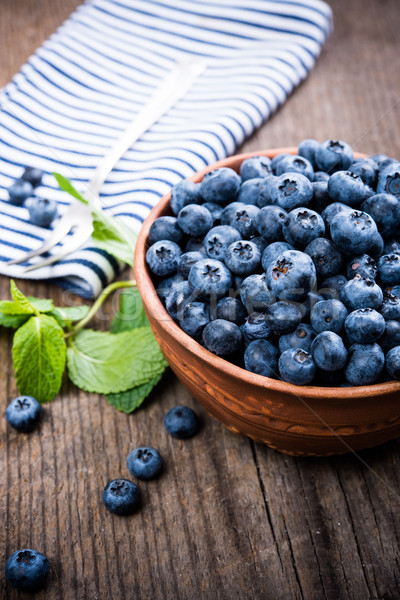 Full bowl of fresh ripe blueberries on old wooden board Stock photo © manera