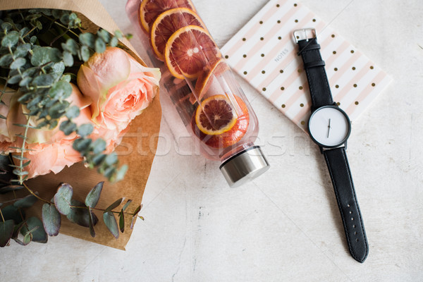 Stock photo: Feminine tabletop, flowers, water with fruits and watch