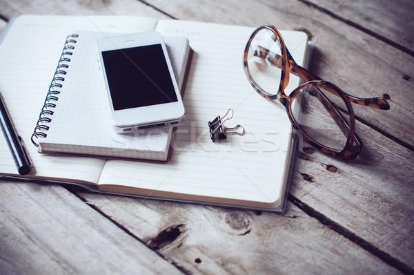 Hipszter otthoni iroda papírok jegyzetfüzetek olvasószemüveg okostelefon Stock fotó © manera