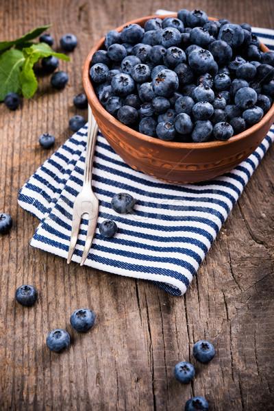 Stock photo: Full bowl of fresh ripe blueberries on old wooden board