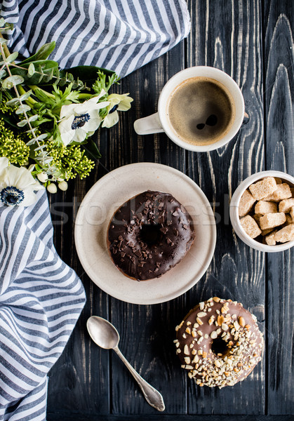 Stock photo: Cup of coffe and a chocolate donuts on black wood