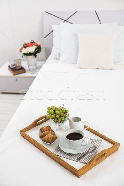 Reggeli ágy tálca kávé gyümölcsök croissantok Stock fotó © manera