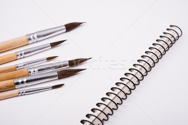 Watercolor paint brushes and clean paper on artist's work desk Stock photo © manera