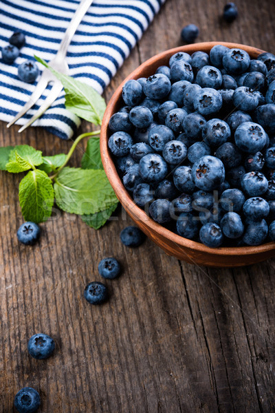 Stock photo: Full bowl of fresh ripe blueberries on old wooden board