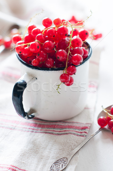Stock photo: red currants in a white enamel mug