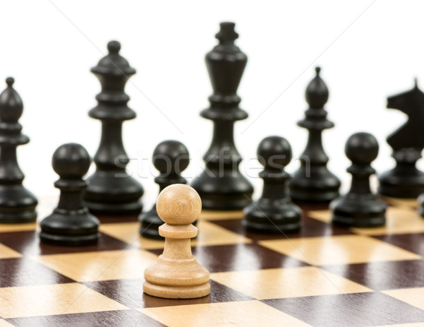 White pawn against a superiority of black chess pieces Stock photo © manfredxy