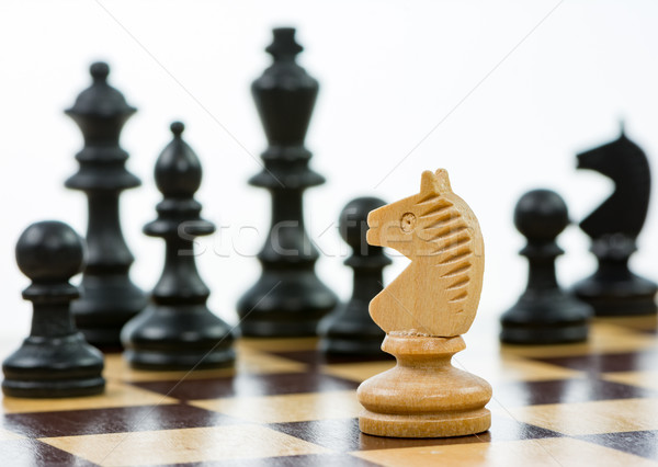 Stock photo: White knight against a superiority of black chess pieces