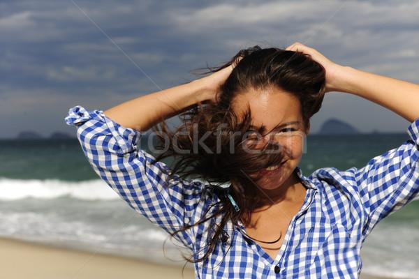 Viharos szél fúj nő fiatal nő tengerpart Stock fotó © mangostock