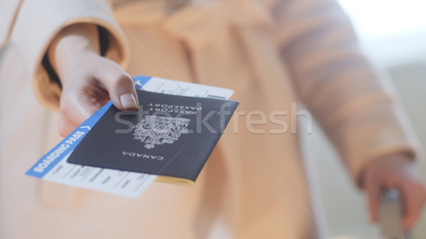 Girl holds Canadian passport and boarding pass Stock photo © Margolana