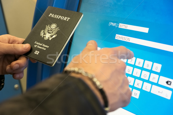A man with a US passport and boarding pass fills the electronic  Stock photo © Margolana