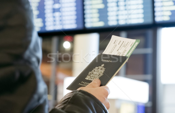 Man with a Canadian passport and boarding pass looks departure Stock photo © Margolana