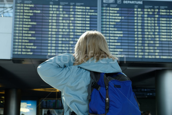 A woman with a backpack looks at departure board Stock photo © Margolana