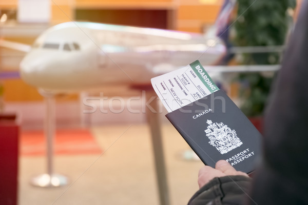 A man with a Canadian passport and boarding pass looks departure Stock photo © Margolana