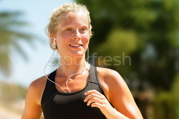Running girl sweating workout with earphones Stock photo © Maridav