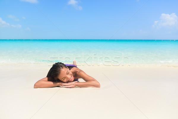 Relaxing woman on beach vacation sleeping on sand Stock photo © Maridav