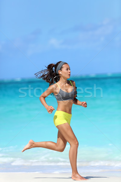 Active lifestyle - woman running barefoot on beach Stock photo © Maridav