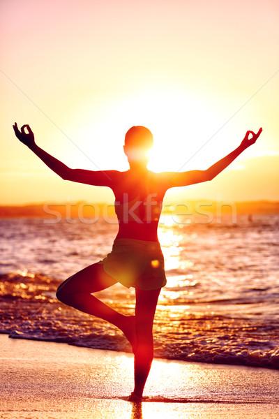 Wellness of mind - Yoga woman standing on one leg doing tree pose Stock photo © Maridav