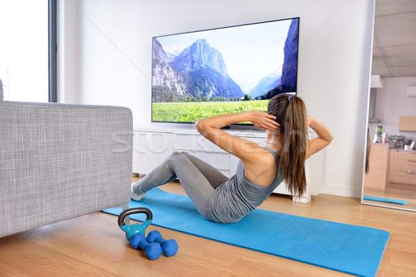 Home workout - woman exercising in front of TV Stock photo © Maridav