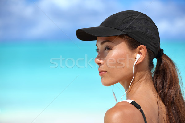 Fitness runner girl listening to music on beach Stock photo © Maridav