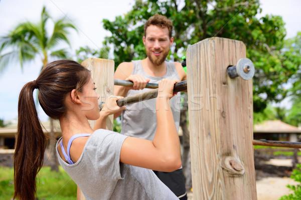 Fitness couple training on chin-up bar together Stock photo © Maridav