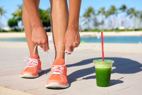 Running woman runner with green vegetable smoothie Stock photo © Maridav