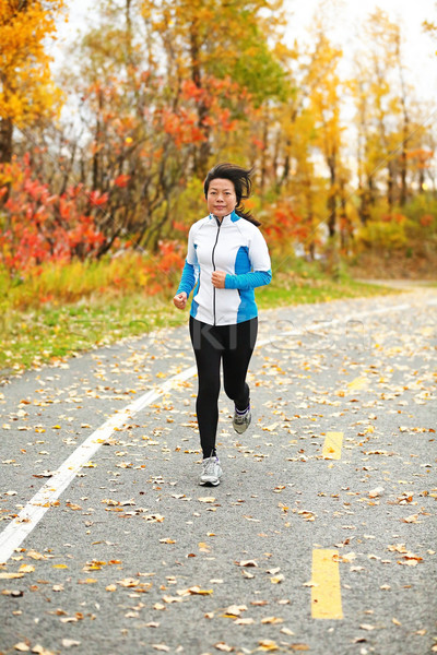 Middle aged Asian woman running active in her 50s Stock photo © Maridav