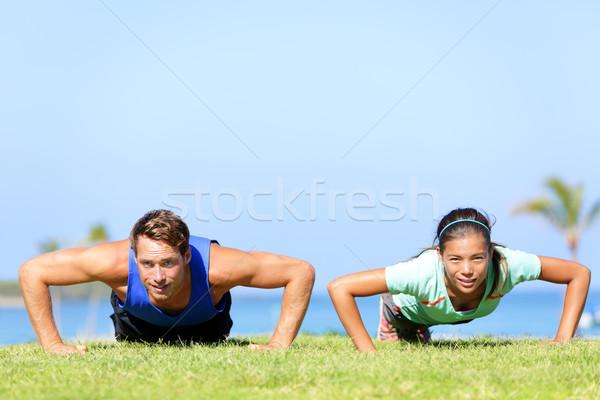Sport fitness couple doing push ups Stock photo © Maridav