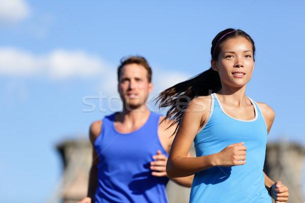 Running couple jogging outside in city Stock photo © Maridav