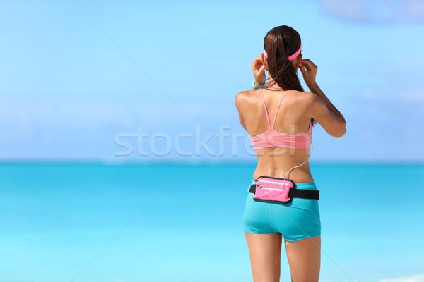 Fitness girl listening to music with earphones Stock photo © Maridav
