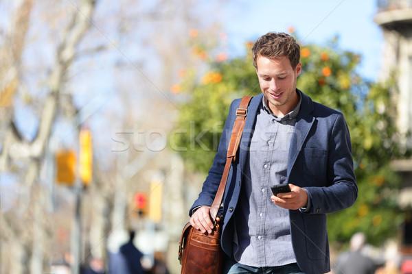 Young urban professional man using smartphone app Stock photo © Maridav