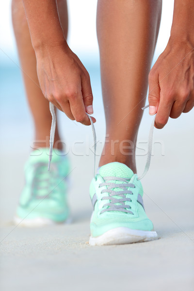 Sportswoman runner getting ready tying running shoes on beach Stock photo © Maridav