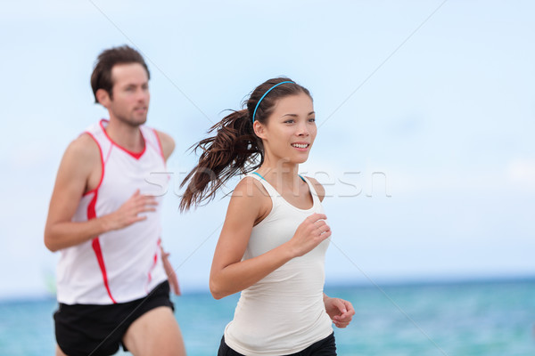 Fitness interracial runner couple running on beach Stock photo © Maridav