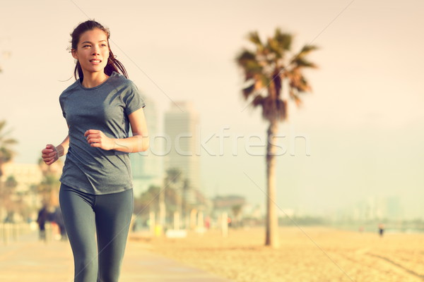 Running woman jogging on beach boardwalk Stock photo © Maridav