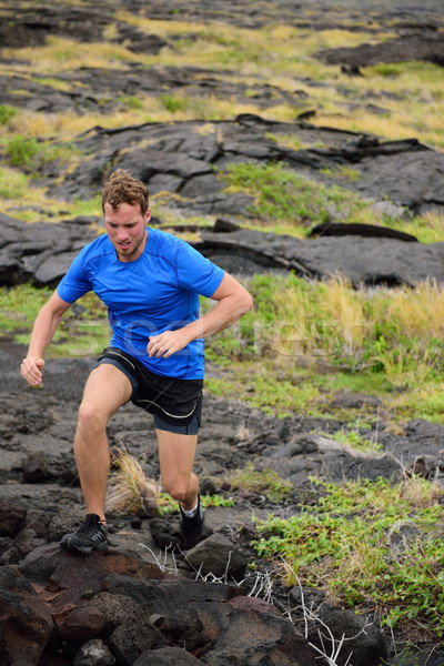 Active man trail running on volcanic rocks Stock photo © Maridav