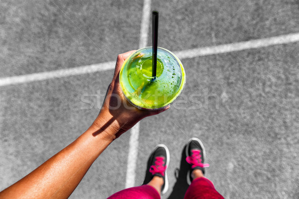 Green smoothie running woman drinking cup to go Stock photo © Maridav
