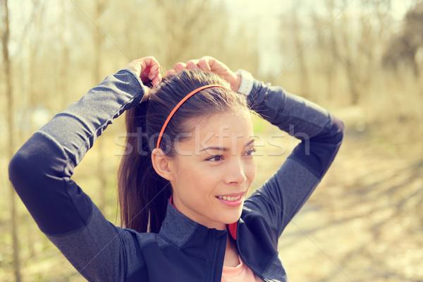 Woman tying hair in ponytail getting ready for run Stock photo © Maridav